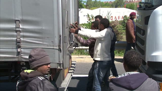exterior shots of migrants opening a the back of a lorry waiting in queue and trying to get into it pan to police searching lorries further down the... - calais stock videos & royalty-free footage