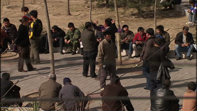 exterior shots of migrants sat and stood around in the street waiting for work on march 16 2009 in beijing china - lavoratore emigrante video stock e b–roll