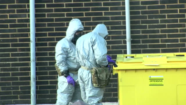 exterior shots of military personnel wearing protective clothing preparing to remove a potentially contaminated ambulance from an ambulance station... - 武力攻撃点の映像素材/bロール
