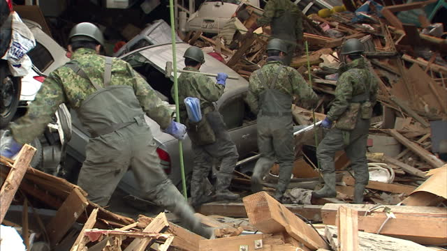 Exterior shots of military rescuers sifting through rubble from completely destroyed buildings and cars after an earthquake tsunami hit the area...