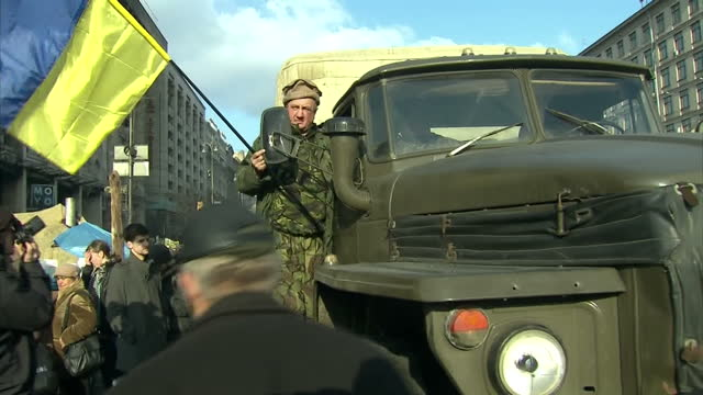 Exterior shots of military vehicle arriving in to Independence square man holding Ukraine flag on vehicle on February 24 2014 in Kiev Ukraine