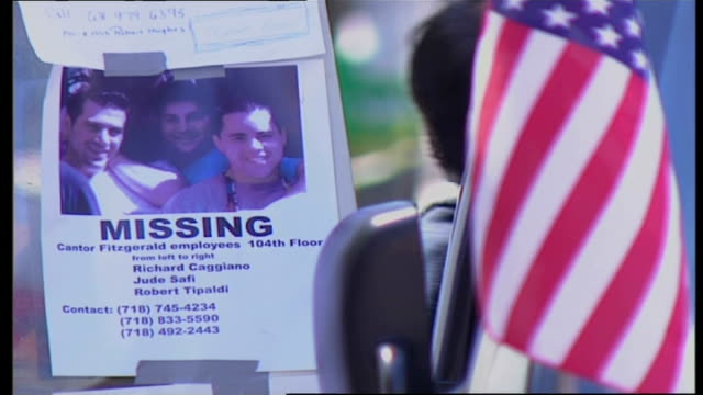 exterior shots of 'missing' posters featuring some of the 9/11 victims on a wall with people looking at them and lots of floral tributes and candles... - al qaida stock videos & royalty-free footage