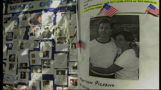 exterior shots of 'missing' posters featuring some of the 9/11 victims on a wall with people looking at them and lots of floral tributes and candles... - outdoor poster stock videos & royalty-free footage