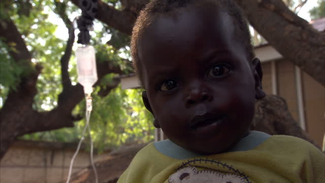 stockvideo's en b-roll-footage met exterior shots of mothers young children waiting for medical attention at a women's clinic in southern sudan southern sudan's 2010 bid for... - hongerig