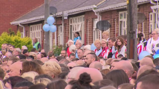 Exterior shots of mourners stood by a roadside as audio of the funeral of Bradley Lowery is played out on 14 July 2017 in Sunderland United Kingdom