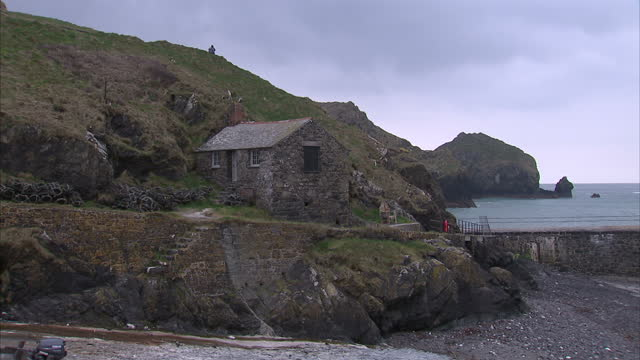 vidéos et rushes de exterior shots of mullion harbour surrounding clifffs shore and fishermen boats on the beach on march 16 2015 on the lizard peninsula in cornwall... - entourer