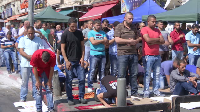 exterior shots of muslims at prayer in a jerusalem street behind a closed security checkpoint in the road, watched by armed israeli police and... - イスラエルパレスチナ問題点の映像素材/bロール