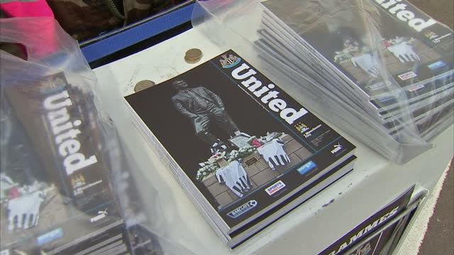 exterior shots of newcastle united football fans arriving at st james' park and match programmes for sale showing a photograph of tributes to mh17... - st. james' park newcastle upon tyne stock videos & royalty-free footage