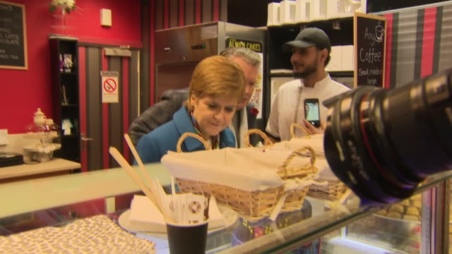 exterior shots of nicola sturgeon visiting a syrian baker, handing out a cake made for her with scottish flags and the snp symbol and trying some of... - nicola sturgeon stock videos & royalty-free footage