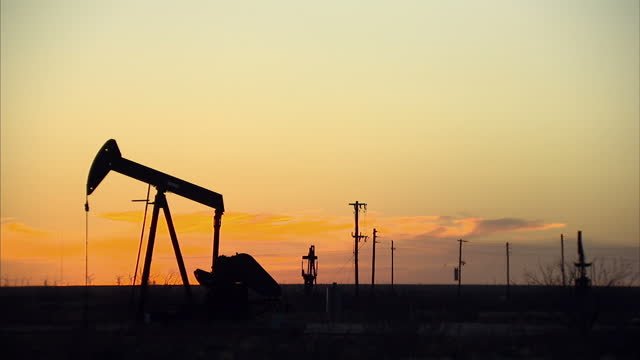 Exterior shots of nodding donkeys in action on a Texan oilfield at sunset bobbing up and down as they work to pump oil on December 19 2014 in Midland...