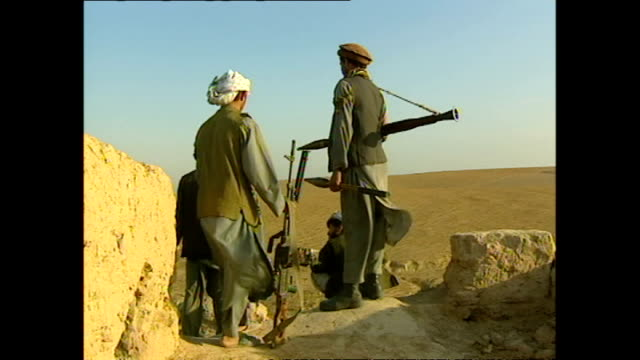 exterior shots of northern alliance soldiers on guard over a barren mountain landscape with rifles during the 2001 us uk led invasion of afghanistan... - 2001 stock videos & royalty-free footage