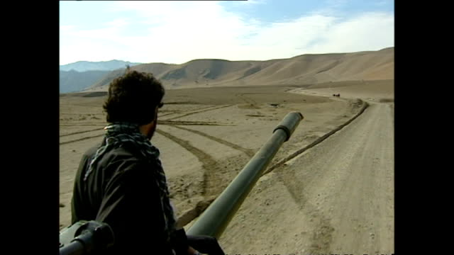 exterior shots of northern alliance soldiers on tanks and trucks passing, close to the white mountains on october 29, 2001 in kabul, afghanistan. - afghanistan stock videos & royalty-free footage