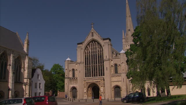 exterior shots of norwich cathedral on a sunny day with clear blue sky and people walking about cathedral area exterior shots of norwich cathedral on... - norwich england bildbanksvideor och videomaterial från bakom kulisserna