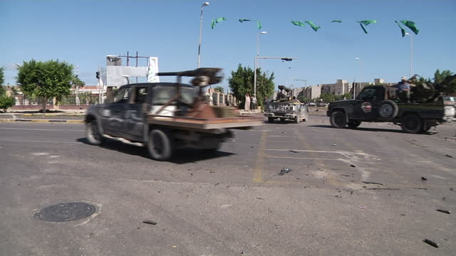 exterior shots of ntc rebels fighting libyan forces to take the city of sirte rebel forces are armed with tanks weapons on trucks guns rpgs libya the... - libya stock videos and b-roll footage