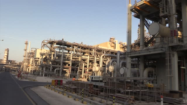 Exterior shots of oil pipelines refinery chimneys and oil workers at a Ras Laffan oil refinery on December 22 2014 in Ras Laffan Qatar