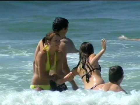 Exterior shots of on a beach in Queensland including shots of people sunbathing playing in the water and preparing to go surfing>> on July 22 2014 in...