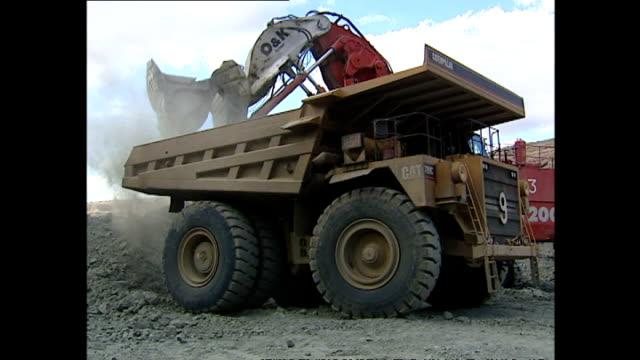 Exterior shots of open cast mining activity at a diamond mine with rock being removed by diggers and removed by dump trucks for crushing on June 07...