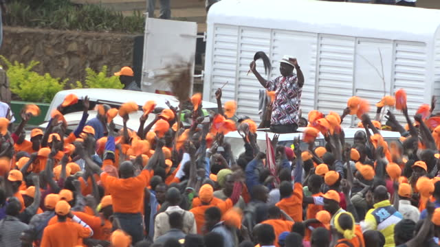 exterior shots of orangeclad supporters of raila odinga's odm party cheering as raila odinga passes waving from the sunroof of a car on 25 october... - raila odinga stock videos and b-roll footage