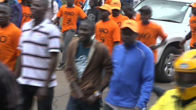 exterior shots of orangeclad supporters of raila odinga's odm party singing and dancing in a peaceful demonstration as soldiers watch on on 25... - raila odinga stock videos and b-roll footage