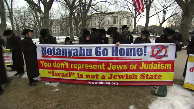 stockvideo's en b-roll-footage met exterior shots of orthodox jewish men protesting against a visit to washington dc by benjamin netanyahu holding banners proclaiming 'netanyahu go... - orthodox jodendom
