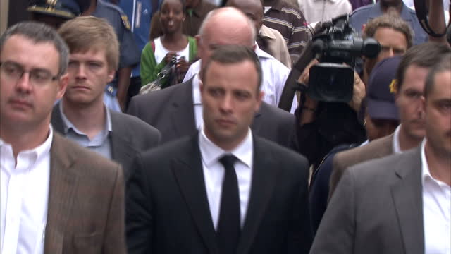 stockvideo's en b-roll-footage met exterior shots of oscar pistorius arriving at court walking down street towards camera flanked by minders and enters the court on april 09 2014 in... - gauteng provincie