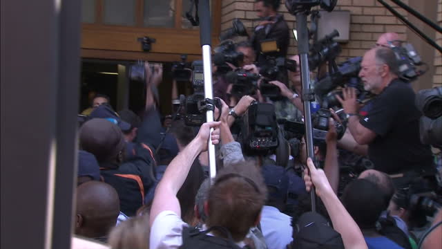 exterior shots of oscar pistorius arrivingt at court getting out of car and walk through media scrum of reporterstv crews and photographers into... - ピストリウス恋人射殺事件点の映像素材/bロール