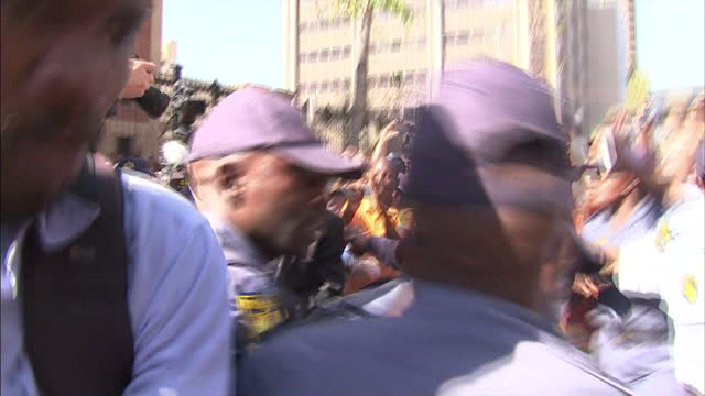 exterior shots of oscar pistorius leaving court building and walk through media scrum with security team past the cameras and into the waiting car on... - スクラム点の映像素材/bロール