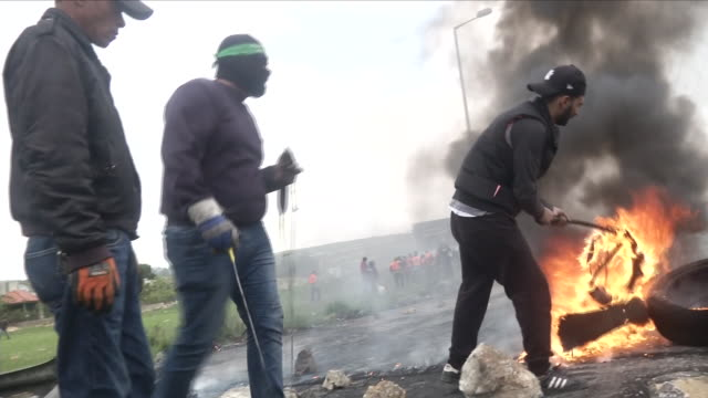 exterior shots of palestinian youths laying burning tyres and rocks across a road near the gazaisrael border during protests along the border>> on... - 2018 gaza border protests stock videos & royalty-free footage
