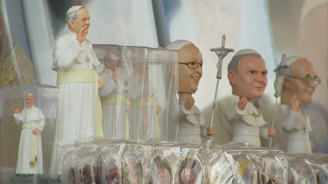 exterior shots of papal memorabilia and souvenirs on sale at a souvenir stand outside the vatican as tourists browse through them on april 26 2014 in... - christianity stock videos & royalty-free footage