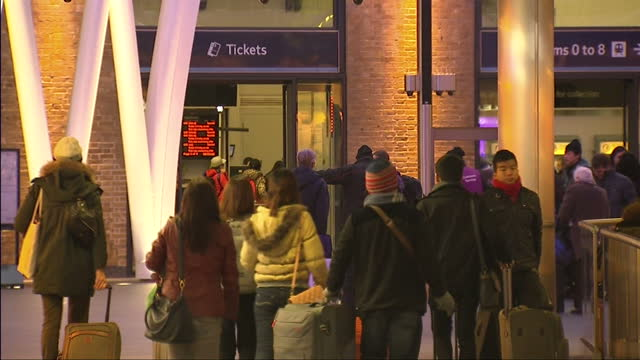 Exterior shots of passengers walking into King's Cross station with luggage during a day of severe rail disruption due to overrunning engineering...