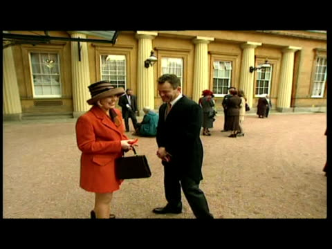 exterior shots of paul burrell & lisa potts posing with george medals in front of photographers and press. - collaboratore domestico video stock e b–roll