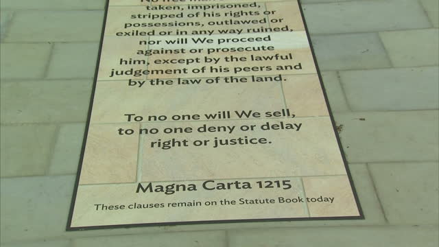 vídeos de stock e filmes b-roll de exterior shots of paving slabs commemorating the magna carta and listing a timeline of the british monarchy from the beginning of edward the... - magna carta documento histórico