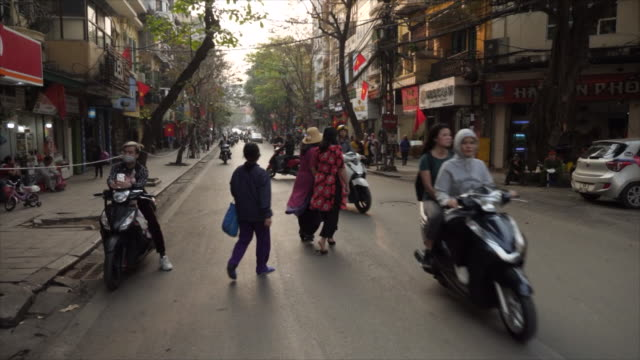 exterior shots of pedestrians mopeds and other traffic passing along a hanoi city road and a vietnamese flag flying on a flower stand on 27 february... - 首脳会議点の映像素材/bロール