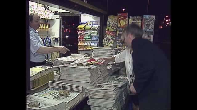 vídeos y material grabado en eventos de stock de exterior shots of people buying newspapers from a kiosk in the street with newspaper headlines covering the divorce of charles and diana prince and... - problemas de parejas