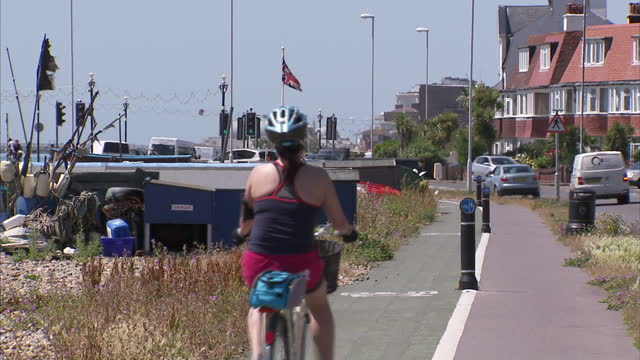 exterior shots of people cycling along worthing seafront in the sunshine past a sign for worthing town on 10 july 2015 in worthing, united kingdom - worthing点の映像素材/bロール
