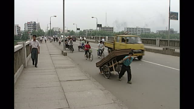 exterior shots of people cycling & pullign a cart down jingdezhen street on may 08, 1998 in jingdezhen, jiangxi province, china. - broth stock videos & royalty-free footage