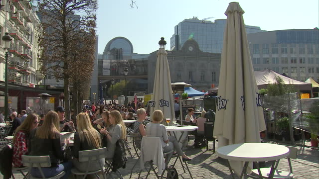 exterior shots of people dining outside a restaurant and of traffic and pedestrians travelling down a cobbled street outside the buildings of the eu... - cobblestone stock videos & royalty-free footage