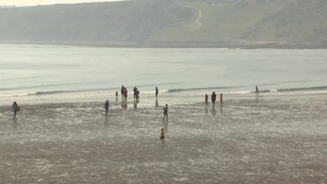 vídeos de stock e filmes b-roll de exterior shots of people enjoying a day by the water hot day on the beach on 20th april 2019 in scarborough england - scarborough reino unido
