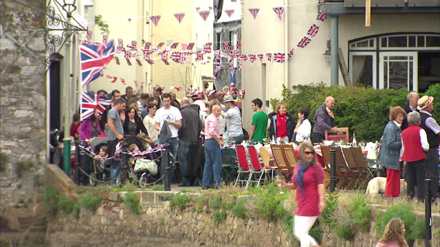 exterior shots of people enjoying exeter street party to celebrate queen elizabeth ii diamond jubilee. people at exeter jubilee street party on june... - exeter england stock videos & royalty-free footage