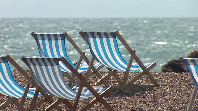 exterior shots of people enjoying sunny weather on the brighton seafront including shots of deckchairs on the beach sailing boats on the water and... - outdoor chair stock videos & royalty-free footage