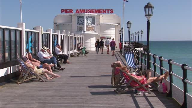 exterior shots of people enjoying the sunshine in worthing, walking along the promenade, beach and the pier on 10 july 2015 in worthing, united... - worthing点の映像素材/bロール