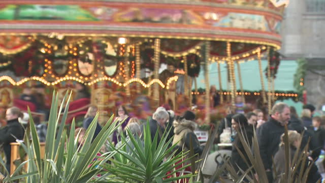Exterior shots of people enjoying themselves at Christmas market carousel going round and people drinking mulled wine on December 20 2016 in...