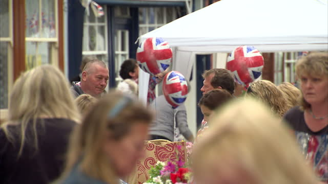 exterior shots of people gathered on streets of exeter at jubilee street parties with bunting and great britain flags decorating people and items... - street party stock videos and b-roll footage