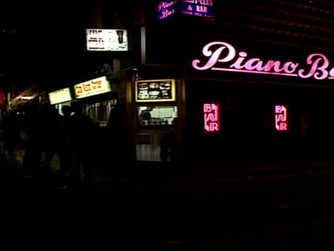 exterior shots of people gathered outside piano bar and madame jojo bars with neon lights and signs for video and mags. bars at night in soho area on... - omosessualità video stock e b–roll