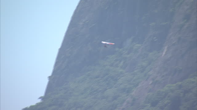 exterior shots of people hang gliding down the mountainside and landing on rio de janeiro beach as seen from the royal tulip hotel build up to 2014... - hang gliding stock videos and b-roll footage