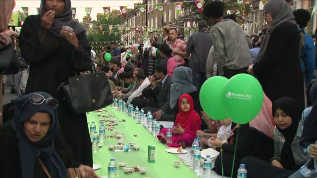 Exterior shots of people in the street outside Finsbury Park Mosque having an evening Iftar meal at an event marking one year since the terror attack...