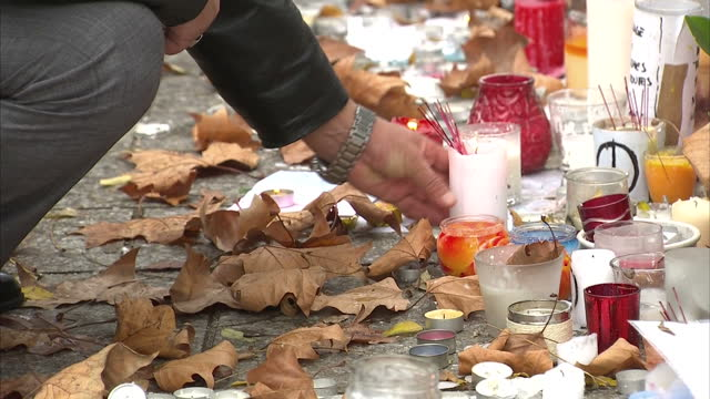 vidéos et rushes de exterior shots of people laying floral and candle lit tributes outside the bataclan theatre hall where an isis terrorist attack took place filmed on... - bombardement