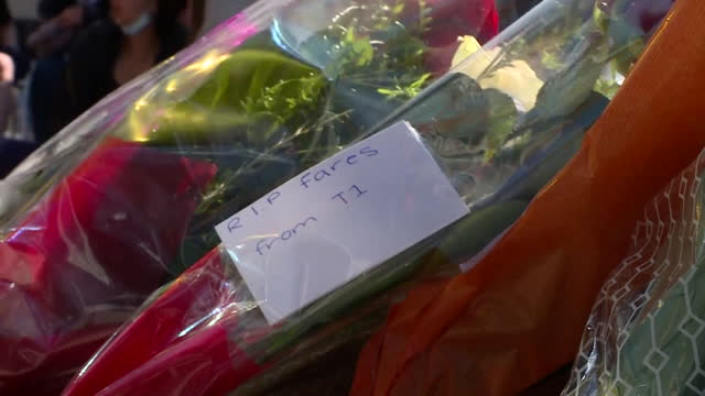 exterior shots of people laying flowers and tributes at the scene of a fatal stabbing of fares maatou, a 14-year-old boy outside a pizza restaurant... - 刺傷事件点の映像素材/bロール