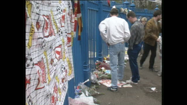 stockvideo's en b-roll-footage met exterior shots of people leaving tribute flowers and messages on the hillsborough stadium railings outside following the hillsborough disaster where... - fa cup