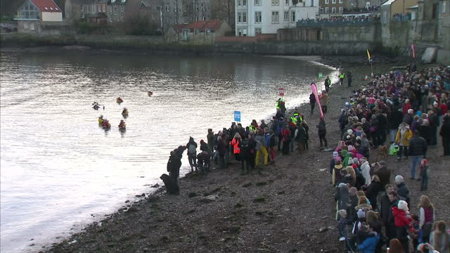 vidéos et rushes de exterior shots of people lined up on banks of fife of forth river and people in life jackets in water for swimming event to start and people waiting... - file attente